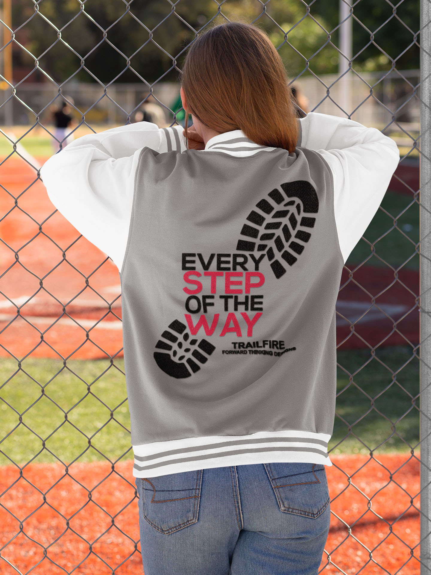 Spredshirt-Prints-Trailfire_0010_mockup-of-a-young-woman-with-a-varsity-jacket-watching-a-baseball-game-33208