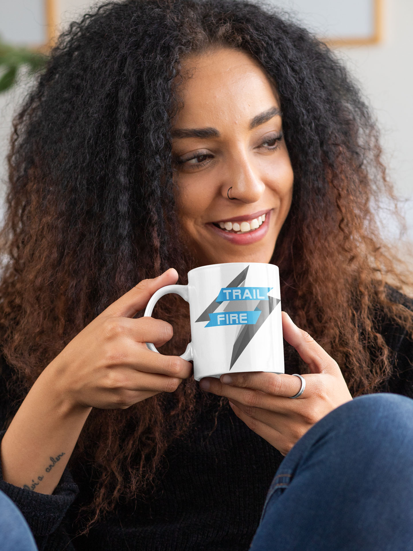 Spredshirt-Prints-Trailfire_0029_mockup-of-a-curly-haired-woman-with-an-11-oz-mug-in-her-hands-33174