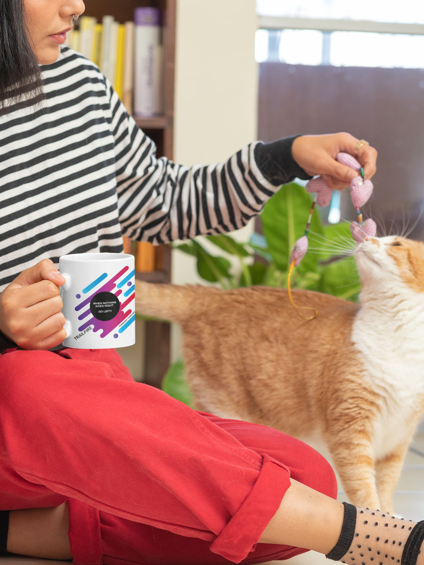 Spredshirt-Prints-Trailfire_0050_11-oz-mug-mockup-of-a-woman-playing-with-her-cat-at-home-30667